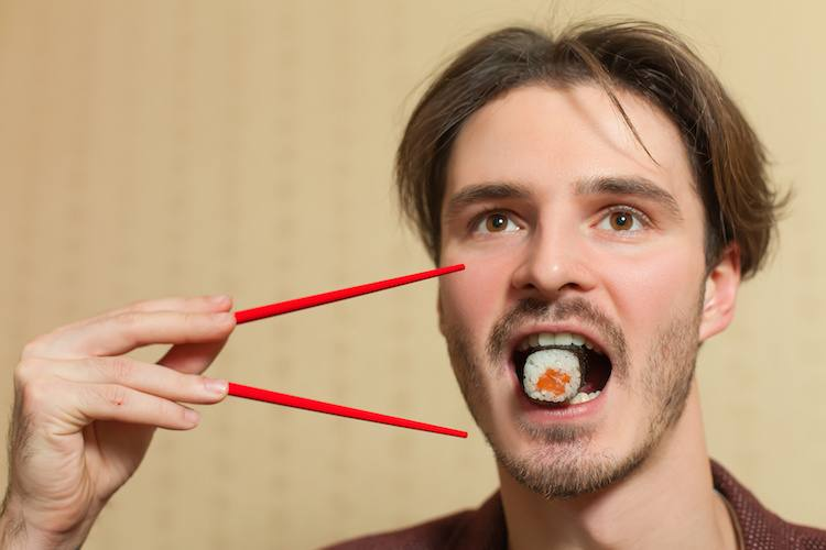 Businessman eat sushi with chopsticks.